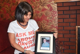 Kathy MacNaughton holds a photo of her late partner David Fraser.  FILE PHOTO/ADAM MACINNIS