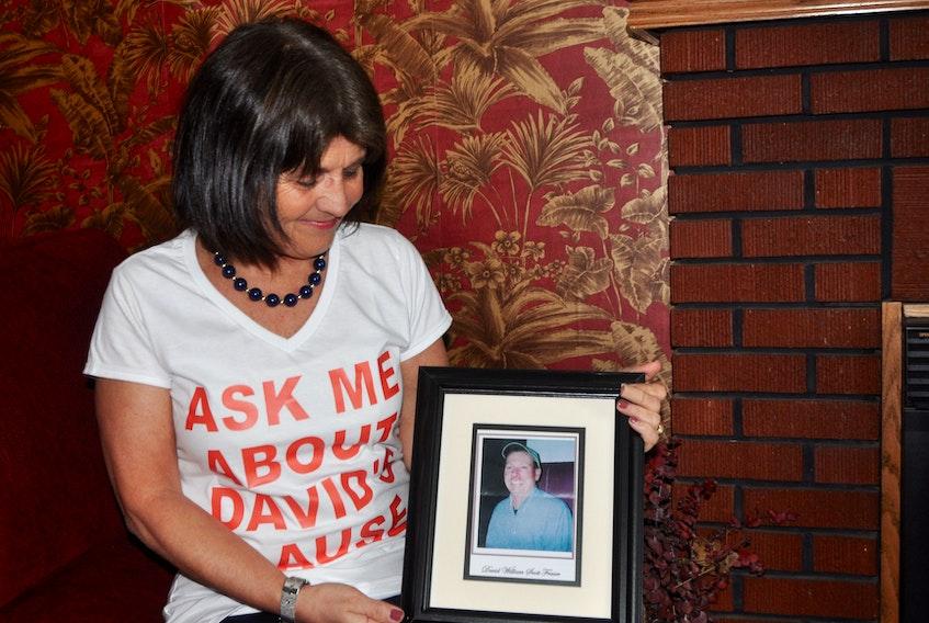Kathy MacNaughton holds a photo of her late partner David Fraser.  FILE PHOTO/ADAM MACINNIS