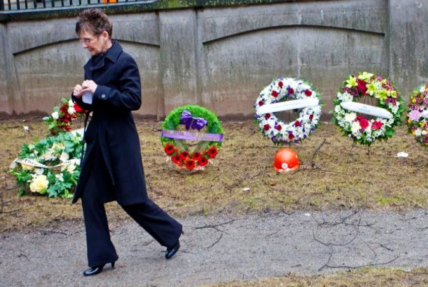 Estella Hickey, mother of Kyle Hickey, who was killed in a workplace accident at O'Regan's Kia in 2008, walks past wreaths laid during a Day of Mourning ceremony at Province House April 28
