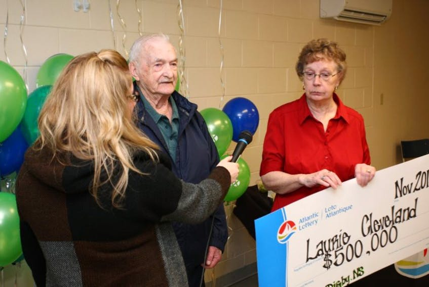 Laurie Cleveland and his wife Sylvia are interviewed by Ashley Dixon of Atlantic Lottery during a cheque presentation in the Digby Curling Club.