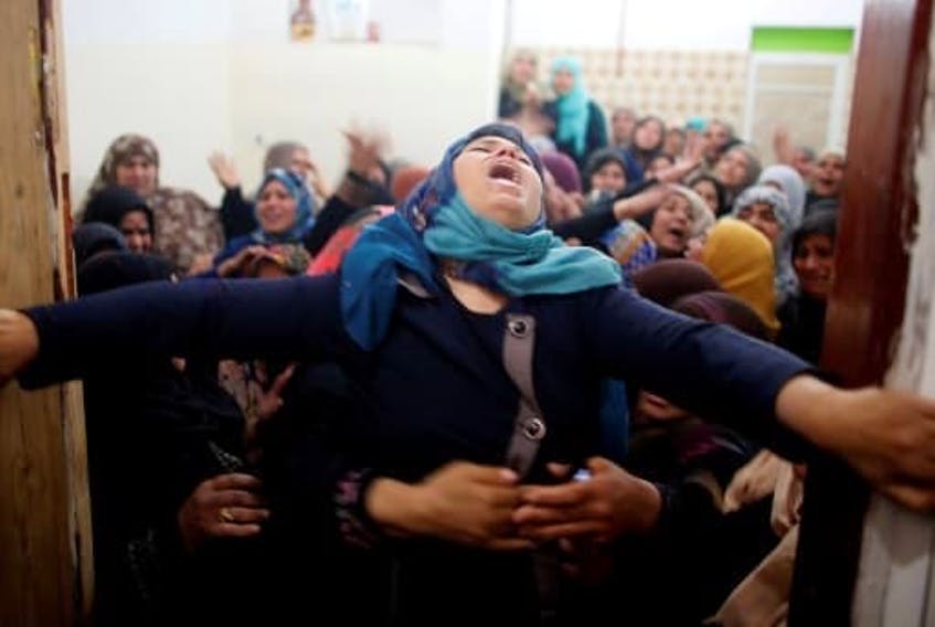Mourners hold back a relative of Palestinian Hamdan Abu Amshah during his funeral in the Gaza Strip, March 31, 2018.   SUHAIB SALEM/ REUTERS