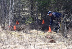 RCMP Sgt. Andrew Buckle marks off a crime scene on Plains Road in Debert as part of the mass shooting investigation.