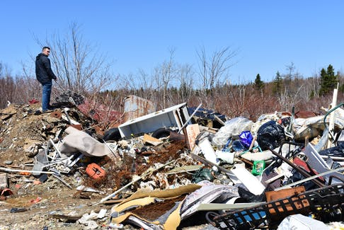In this file photo, Dylan Yates, founder of the Cape Breton Environmental Association, looks over mounds of garbage that were illegally dumped behind the water tower in Reserve Mines. CAPE BRETON POST