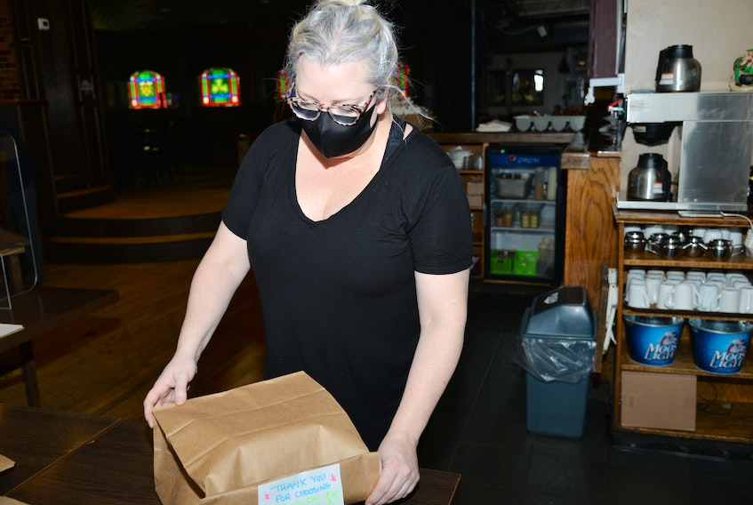 Jillian Campbell of the Olde Dublin Pub prepares a take-out order for a customer on Tuesday during the most recent dining room shutdown. On Wednesday, the province announced it was reopening dining rooms with revised restrictions.