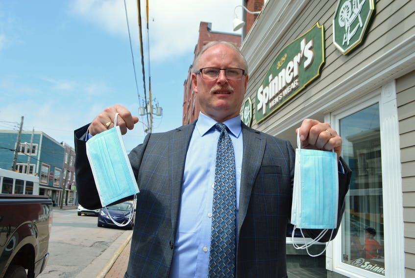 Scott MacVicar, owner of Spinner's Men's Wear on Charlotte Street in Sydney, holds up masks stocked at his store, in preparation for masks becoming mandatory in indoor public places in Nova Scotia today. Some businesses in the Cape Breton Regional Municipality are expressing concerns over what to do if someone does enter their business without a mask on. Sharon Montgomery-Dupe/Cape Breton Post