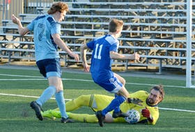 Feildians goalkeeper Braedon Sheppard makes a save as teammate Iain Gamba (7) and the St. Lawrence Laurentians' Cabhan O'Keefe (11) look on during Challenge Cup soccer action at King George V Park Saturday evening. — Keith Gosse/The Telegram