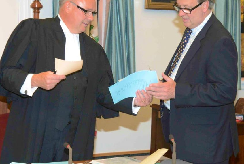 Charlie MacKay, clerk of the P.E.I. legislature, speaks with Health Minister Doug Currie during Tuesday's session.