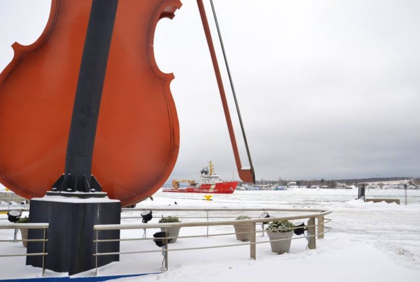 The Canadian Coast Guard vessel Earl Grey makes its way between the body and the bow of the giant fiddle located on the Sydney Marine Terminal. The ship was active in Sydney harbour on Thursday morning clearing ice for the Algoscotia as it left the harbour.