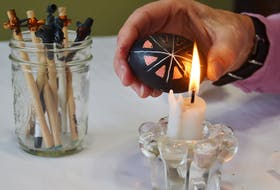 Orysia Dawydiak uses a candle melt to off the wax. It doesn't take long until a beautiful design is revealed. SALLY COLE/THE GUARDIAN