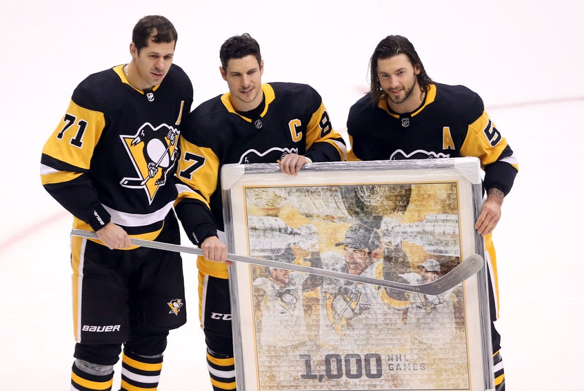 Pittsburgh Penguins centre Evgeni Malkin (71) and defenceman Kris Letang (58) present Sidney Crosby (87) with gifts commemorating his 1,000th career NHL game as a Penguin before playing the New York Islanders at PPG Paints Arena on Saturday. (Charles LeClaire-USA TODAY Sports)