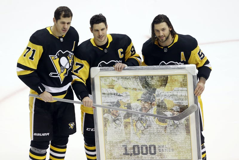 Pittsburgh Penguins centre Evgeni Malkin (71) and defenceman Kris Letang (58) present Sidney Crosby (87) with gifts commemorating his 1,000th career NHL game as a Penguin before playing the New York Islanders at PPG Paints Arena earlier this season - Charles LeClaire