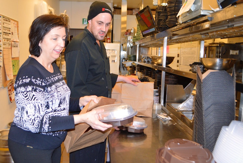 Flo Fogarty, manager of Montana's restaurant on Reeves Street in Sydney, and Logan MacDonald, kitchen manager, work on putting some takeout orders together at the restaurant. Sharon Montgomery-Dupe/Cape Breton Post