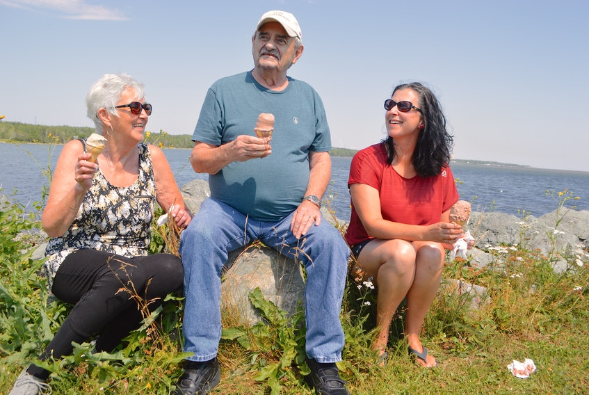 Maurina Canova, left, husband Sheldon and daughter Anna, celebrate the great Cape Breton summer weather with ice cream at the Bayside Drive-In in River Ryan, Monday. The family, which was at Dominion Beach earlier in the day, say they often go out for drives around the area together. Sharon Montgomery-Dupe • Cape Breton Post
