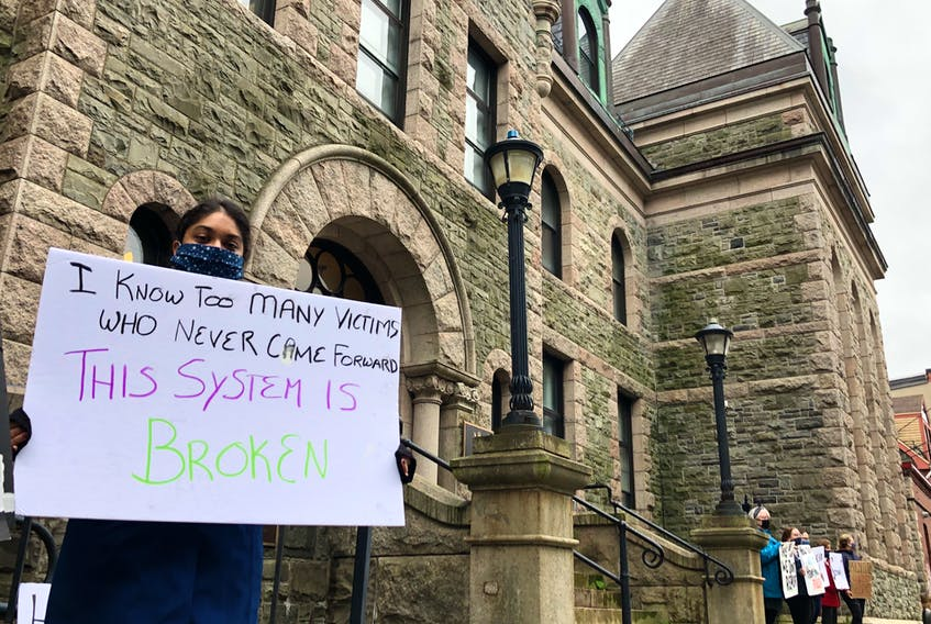 A protester holds a sign outside Newfoundland and Labrador Supreme Court on Duckworth Street in St. John's in early October. The demonstrators called for judicial reform and an end to sexual violence. TELEGRAM FILE PHOTO