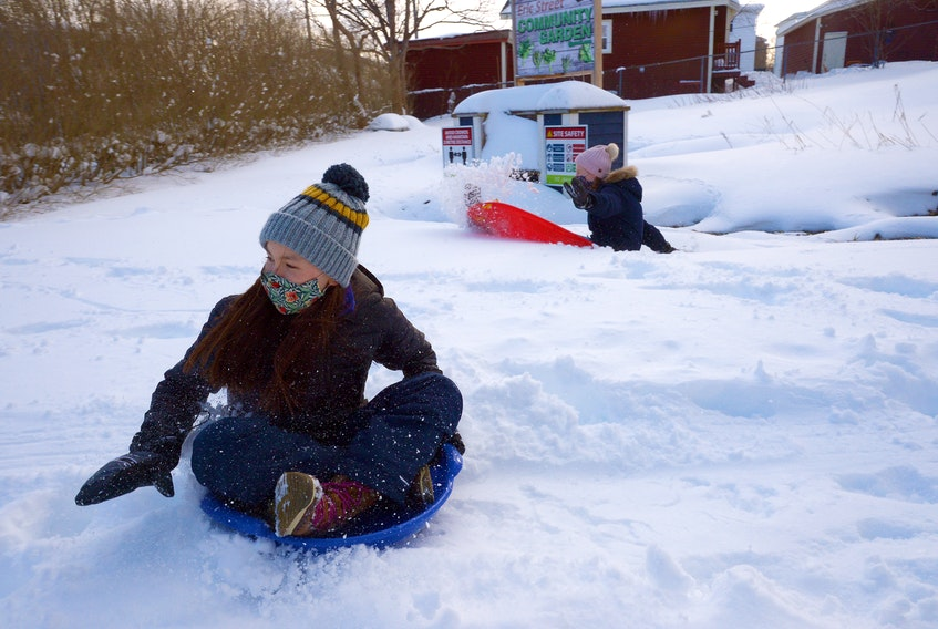 Mia Critch (left) and her friend, Lily Shand, slide on a hill in a lot on Eric Street Thursday afternoon. Residents in the area are upset they may lose the space if the City of St. John's rezones the land to allow for development of three Habitat for Humanity townhouses on the lot. Keith Gosse • The Telegram