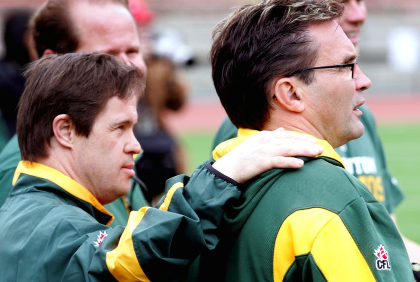 Edmonton Football Club locker-room attendant Joey Moss puts his hand on the shoulder of equipment manager Dwayne Mandrusiak during 2010 training camp at Commonwealth Stadium in this file photo.