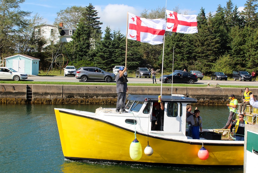 One of the moderate livelihood fishing boats heading out into the St. Peter's Canal in this October 2020 file photo. The boat is flying Mi'kmaq grand council flags as the driver of the boat holds up the tags issued by Potlotek First Nation. CAPE BRETON POST FILE