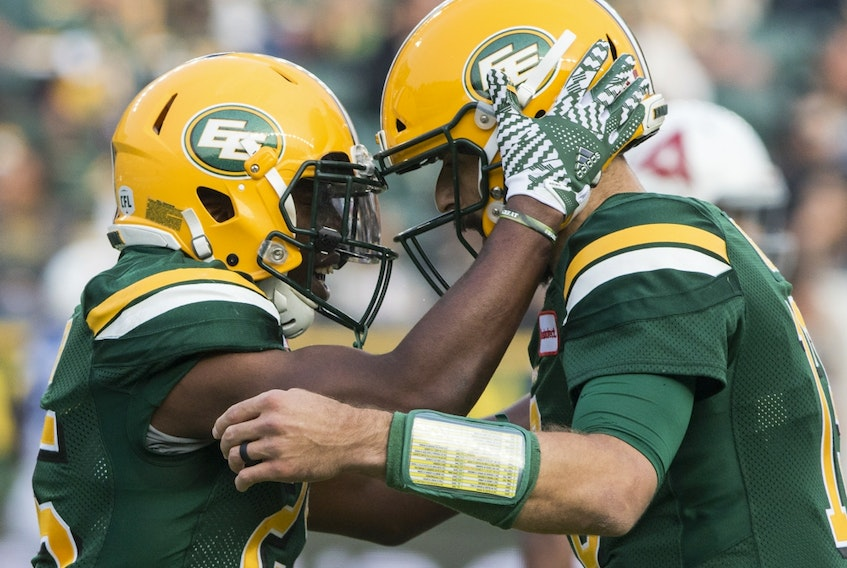 Edmonton Football Team running back Shaquille Cooper (25) celebrates his touchdown against the Montreal Alouettes with quarterback Mike Reilly (13) in this file photo from August 18, 2018, in Edmonton.