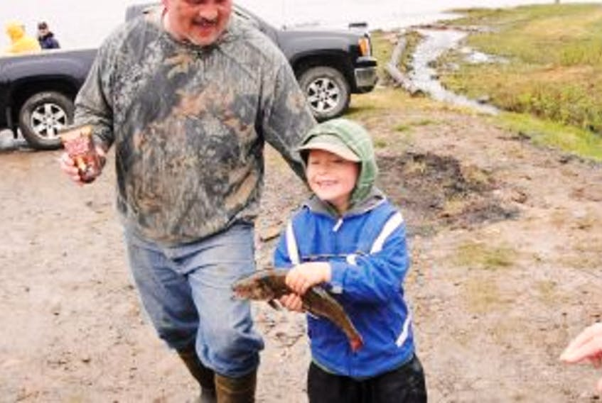 ['<p>Rob Boutilier, president of the Port Morien Wildlife Association, looks on as Kristopher McNeil, of Birch Grove, shows him a fish he caught, in this photo taken during a previous PMWA kids' fishing derby. The Port Morien Wildlife Association's 40th annual kid's fishing derby is being held at Morrison Lake on Sunday from 10 a.m.-2 p.m. and, in keeping with a change the association made to the derbies five years ago, everything is free.</p>']