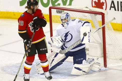The Calgary Flames' Elias Lindholm battles Tampa Bay Lightning goaltender Louis Domingue at the Scotiabank Saddledome in Calgary on Dec. 20, 2018. Darren Makowichuk/Postmedia