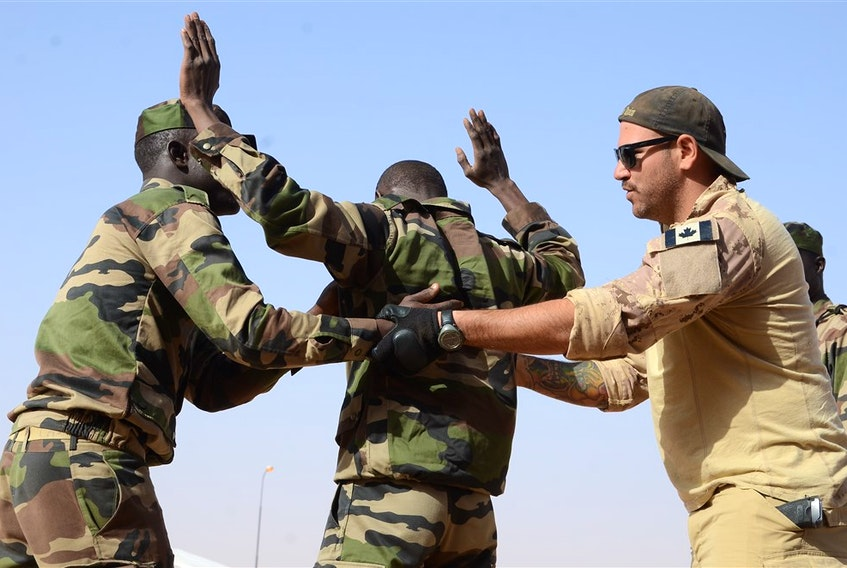 A Canadian Special Operations Regiment instructor teaches soldiers from the Niger Army how to properly search a detainee in Agadez, Niger, Feb. 24, 2014 during that year's Flintlock exercise. (U.S. Army photo)