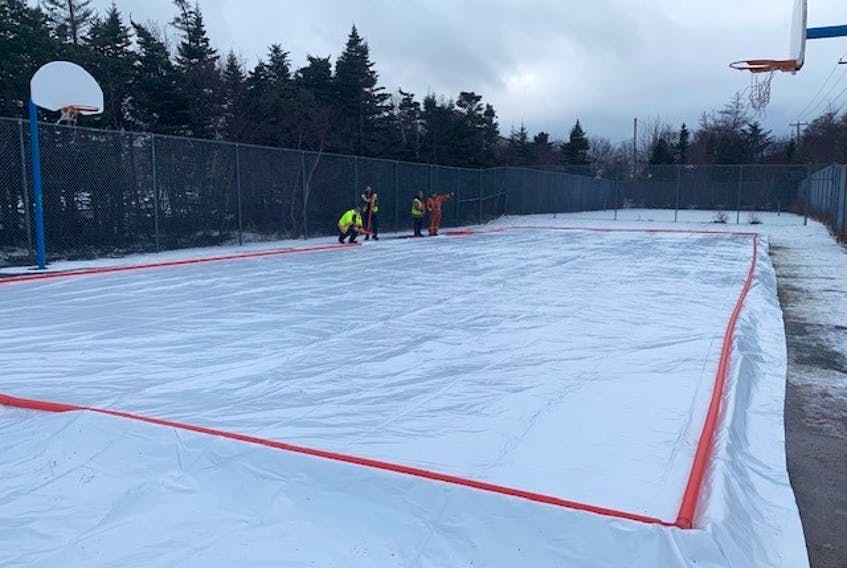 City of Mount Pearl public works staff work on constructing an outdoor skating rink at the basketball courts off Murley Drive last week. It's one of four outdoor rinks the city will have available for public use this winter. — CONTRIBUTED