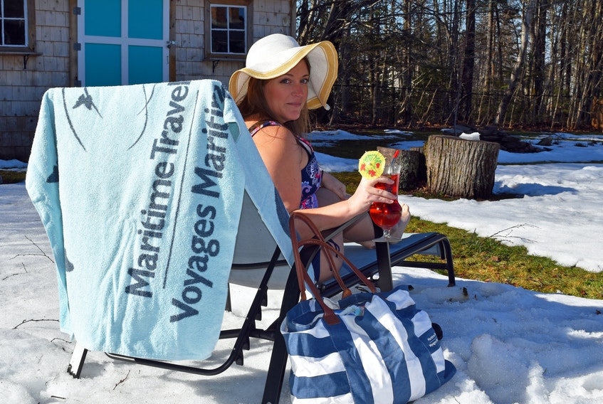 Larissa Newell, branch manager of Maritime Travel in Charlottetown, P.E.I., has been creating fun travel-inspired photographs to help people keep dreaming about travel, including a trip to the beach from her snowy backyard.