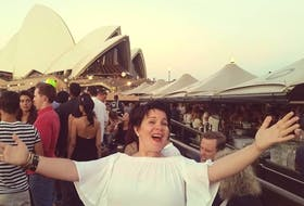 Emilie Chiasson sings outside the Sydney Opera House. With COVID-19 has grounded her in more ways than one - she's purchased her first home.