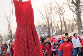 In this file photo, a red dress symbolizing missing and murdered Indigenous women was hung from a stop sign as a solemn group of about 70 people made their way toward Cassidy Bernard's hometown of We'koma'q.