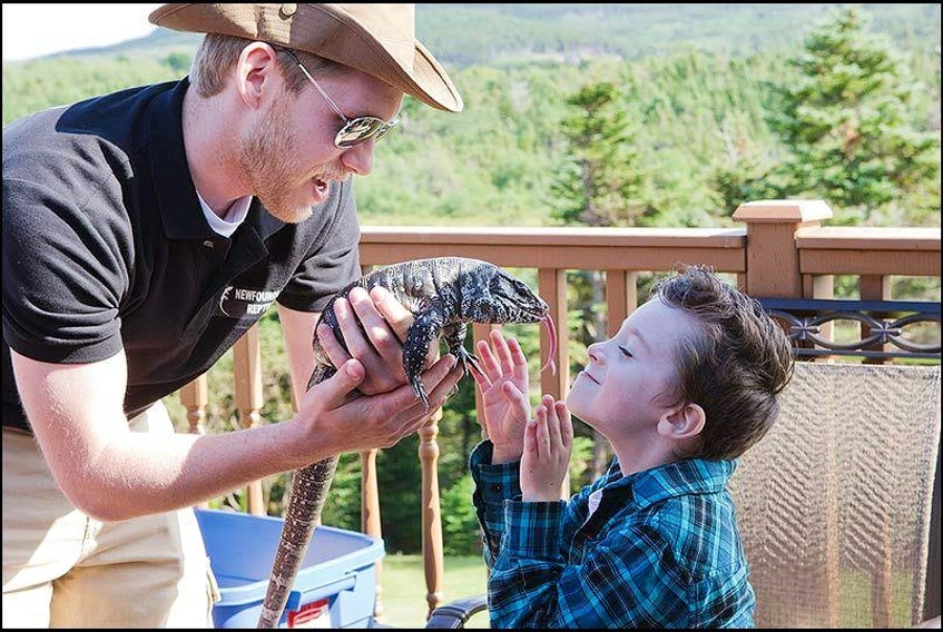 Jelly Bean Entertainment owner Troy Stuckless, from St. John's, introduces Nixon Marsh to one of his reptiles. Stuckless has owned reptiles for 17 years and, for the past decade, has offered reptile education shows.