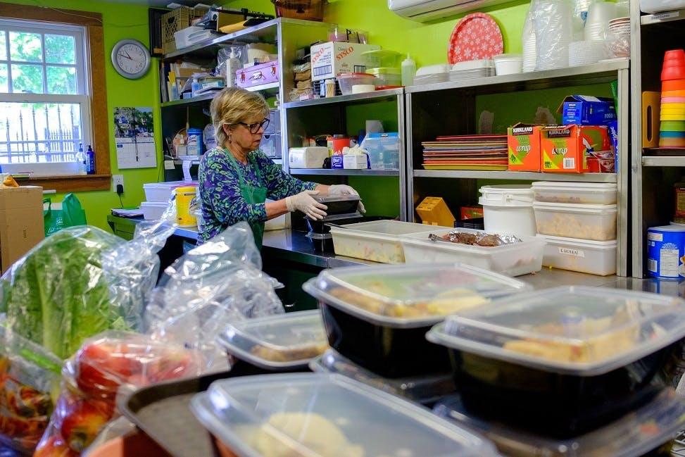 Feeding Others Of Dartmouth (FOOD) Society volunteer Cathy Belanger prepares food to be served as takeout meals in Dartmouth, N.S.