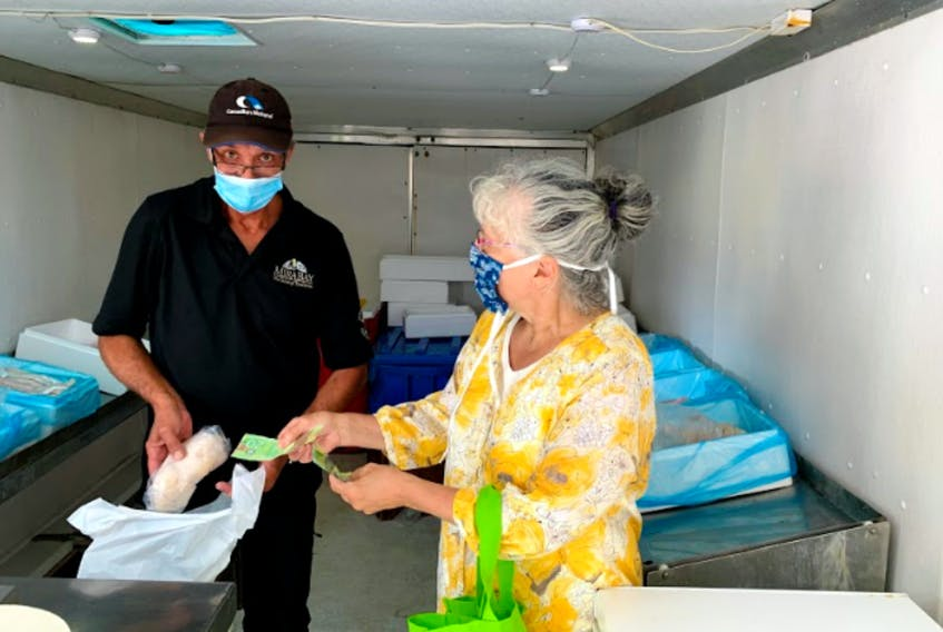 """Dave Nicholson hands over fresh, locally caught fish, to a regular customer of the Mira Bay fish truck owned by Louisburg Seafoods. The truck has become a tradition for the local folk in the communities that dot the coast of Cape Breton. On an average day in Cheticamp, Nicholson said, """"I can see anything from 80 to a couple of hundred customers, in a constant stream coming through the truck."""" Contributed by Shaowei Xu"""
