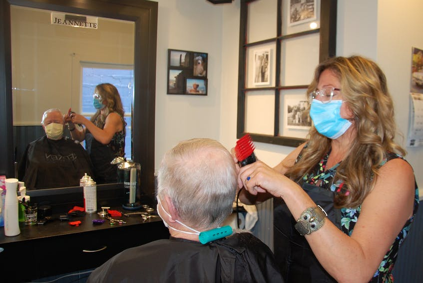 Coralee Schneider cuts Stan MacPhee's hair Friday at the Downtown Barber Shop in Charlottetown. Barbers and hairstylists on P.E.I. dealt with a steady stream of customers on their first day back in business since a mandatory shut-down in mid-March due to the pandemic.