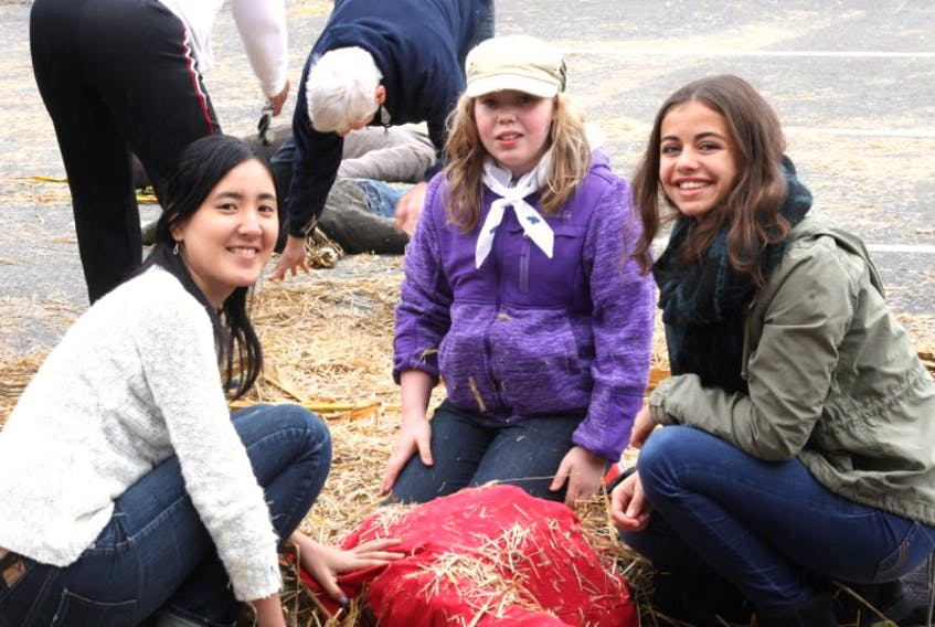 """NKEC students Nanako Miyajima, left, Rachel Turner and Caroline Nothen took part in the pumpkin people-making workshop held as part of the Kentville Harvest Fest Oct. 3. It was their first time taking part in the worskhop. """"WE thought it would be fun, and it was fun,"""" they said."""
