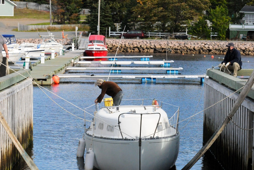 The owner of the sailboat Amanda ties ropes to his craft as it was being prepared for removal from the water at the Holyrood Marina on Wednesday afternoon to be hoisted and carried via a heavy duty lift to its spot for the upcoming winter months. -Joe Gibbons/The Telegram