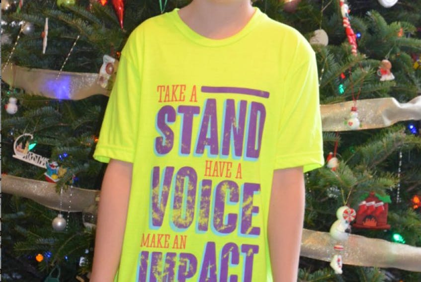 KCA student Gabriel Baker wears a t-shirt with his school's We Day motto – 'Take a Stand, Have a Voice, Make an Impact'. Baker recently raised $101 from a We Day-inspired campaign, which he will donate to the charity We Create Change to purchase two goats.