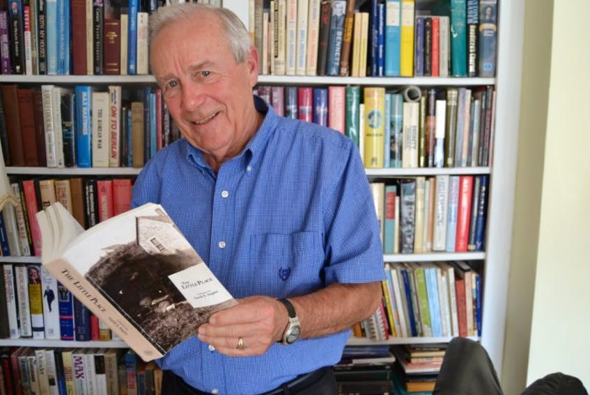 """Garth E. Staples holds a copy of his new book, """"The Little Place: A Memoir by Garth E. Staples"""", in the library of his home on Ambrose Street in Charlottetown. He has written it as a thank-you to all the people he's met in his life."""