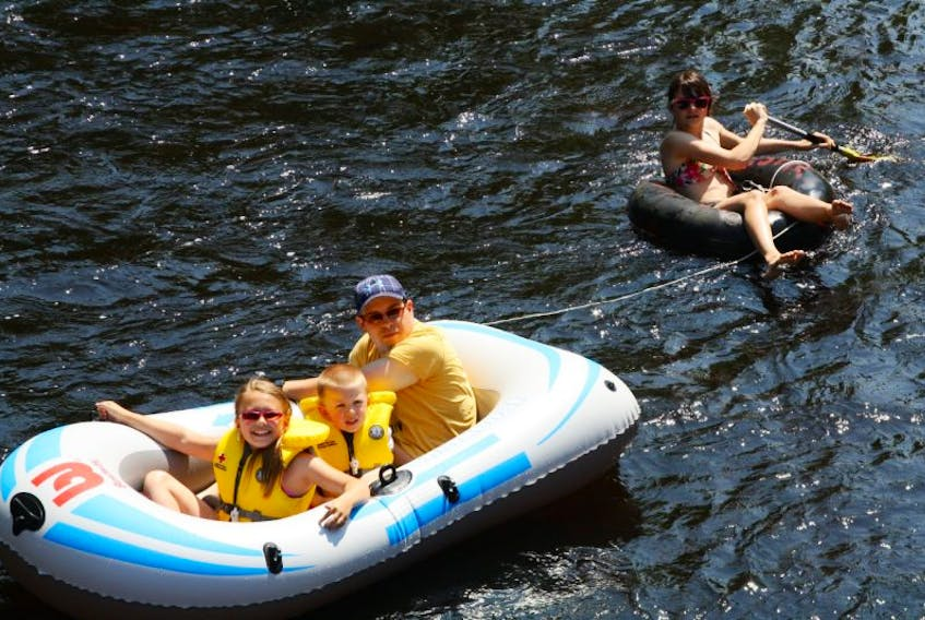 Sandy, Caile, Noah and Alexandria McFadden, Kentville, enjoy one of the summer's most popular activities – tubing down the Gaspereau River