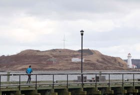 A jogger runs along the Halifax waterfront boardwalk Friday, Dec. 6, with Georges Island in the background.