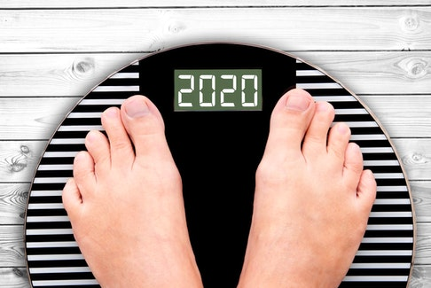 2020 feet on a weight scale on white planks, new year and holiday food nutrition and diet concept.