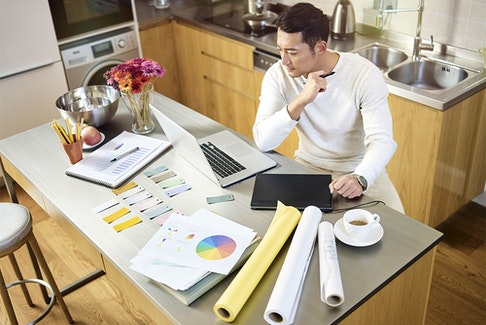 high angle view of a young asian designer sitting at kitchen counter working on a design using laptop computer and digital pen tablet