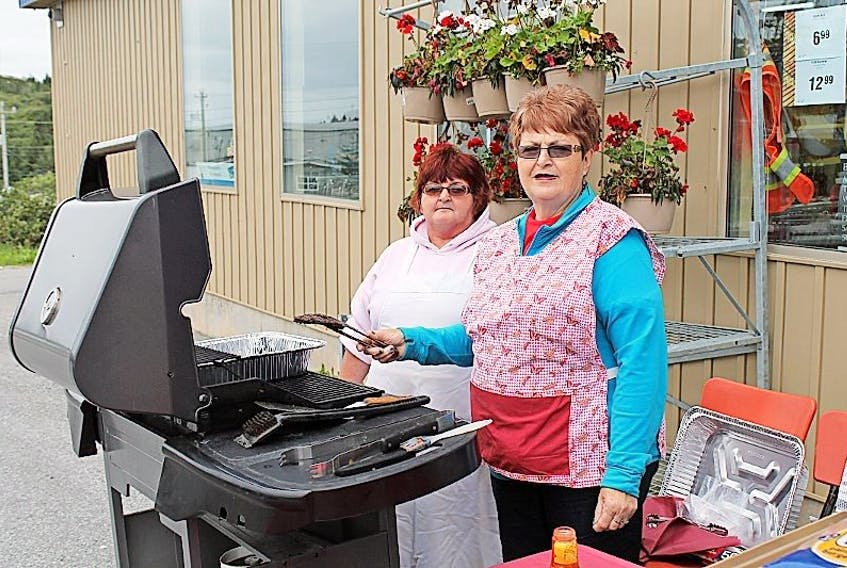 Burgeo Burnette's Laura Hann and Sheila Oxford are pictured preparing food at a fundraising event for the Burgeo Fire Department on Aug. 27. The department is in need of a nozzle for the end of the hose that turns the water into a mist and acts as a shield to help keep heat off the firefighters. The fundraiser was considered a success with the department raising $670.