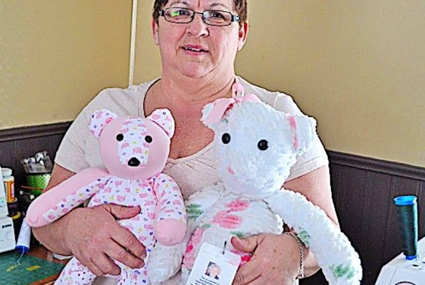 Donna Battiste holds the very first keepsake bear, right, she created along with a recent one.