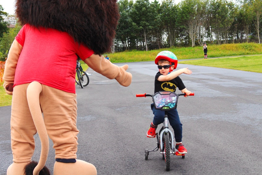 Young Adult Cancer Canada held its Roller Brave fundraising event on Saturday at the track behind St. Paul's Junior High in St. John's. Together, the cross-Canada team of volunteers is going to roll one kilometer for every young adult diagnosed with cancer in Canada every year — 8000. Here, Leo MacDonald gets a high-five from YACC mascot, Razor, for his participation. – Andrew Waterman/The Telegram