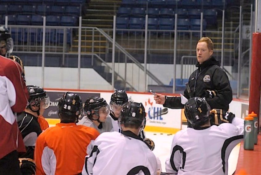 Charlottetown Islanders coach Gordie Dwyer runs through a drill with his players at Tuesday's practice.