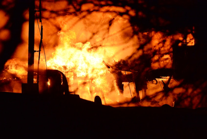 Firefighters battle a blaze at Woodland Farm on Back Line in Goulds Feb. 22. A barn was destroyed and reportedly 70 cows died in the fire.