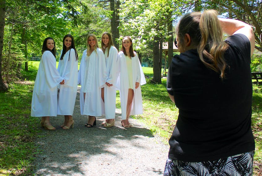 Riverview Rural High School grads Emma MacPhee, from left, Erin MacIsaac, Julia Currie, Gillian Ellerker and Julie MacLeod smile as photographer Anita Clemens takes their photos in Petersfield Provincial Park in Westmount on Tuesday. Chris Connors/Cape Breton Post