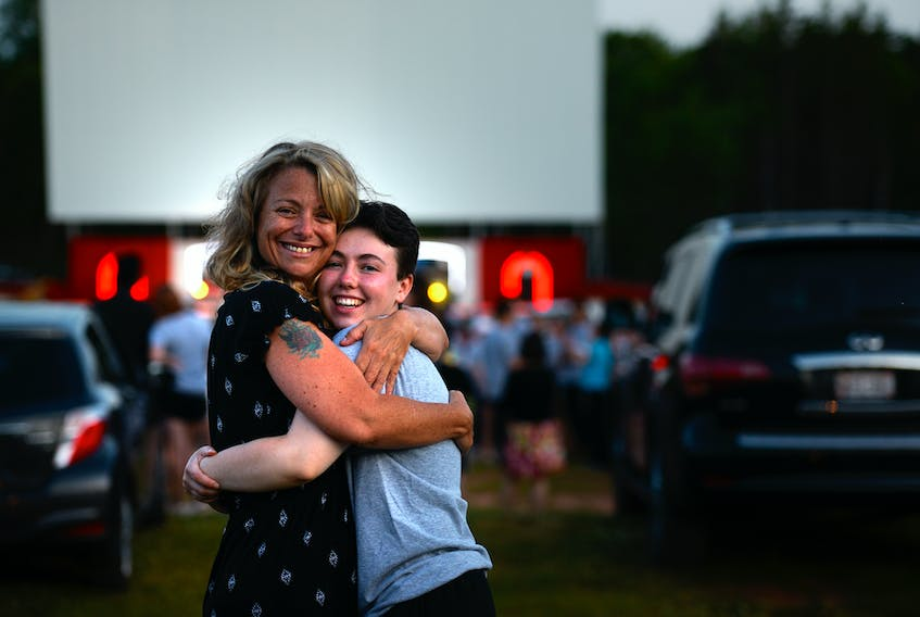 Colonel Gray High School graduate Ken Sillars receives a hug from mom Amy Handrahan at the 2020 graduation ceremony at the Brackley Drive-In on Tuesday.