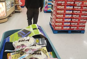 Justin Arsenault walks down a Walmart aisle, cart full behind him, as he stops to buy gifts for the residents of the Chez-Nous Co-Operative.