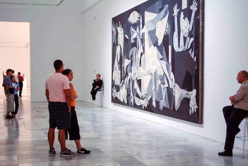 """People visiting Museo Nacional Centro de Arte Reina Sofia stand before the painting by Pablo Picasso """"Guernica""""  commemorating the bombing during the Spanish Civil War."""